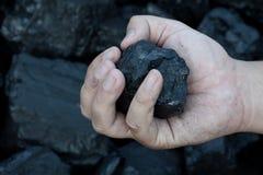 Mão carbonosa que guarda a peça ensolarado da pedra de carvão Imagens de Stock Royalty Free