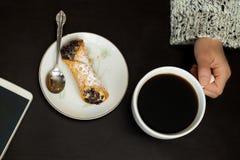 A mão caucasiano da mulher guarda o copo de café com smartphone e o cannoli italiano na placa no fundo preto fotografia de stock royalty free