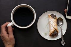 A mão caucasiano da mulher guarda o copo de café e o smartphone com o cannoli italiano na placa no fundo preto imagem de stock