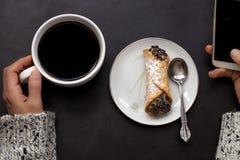 A mão caucasiano da mulher guarda o copo de café e o smartphone com o cannoli italiano na placa no fundo preto fotografia de stock