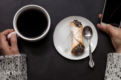 A mão caucasiano da mulher guarda o copo de café e o smartphone com o cannoli italiano na placa no fundo preto fotografia de stock royalty free