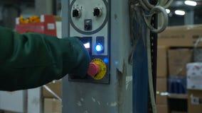 A mão coberta pressiona o botão do poder em uma máquina especial no armazém filme
