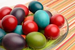 A mão colorida tingiu ovos da páscoa em uma bacia em uma tabela com toalha de mesa listrada. Fotografia de Stock Royalty Free