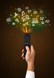 Mão com ícones de controle remoto e sociais dos meios Fotografia de Stock