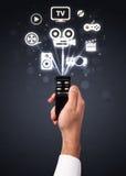 Mão com ícones do controlo a distância e dos meios Imagem de Stock
