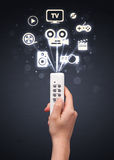 Mão com ícones do controlo a distância e dos meios Fotos de Stock Royalty Free