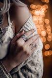 A mão com anéis de prata no bokeh dourado ilumina o fundo Fotos de Stock Royalty Free