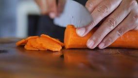 Mão com as cenouras dos cortes da faca vídeos de arquivo