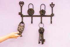 Mão com as chaves de esqueleto antigas de bronze que penduram na parede Foto de Stock Royalty Free