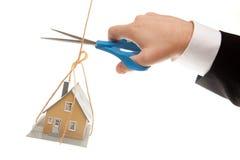 Mão com as tesouras que cortam a casa da terra arrendada da corda Fotos de Stock