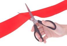 Mão com as tesouras que cortam a fita vermelha Fotografia de Stock Royalty Free