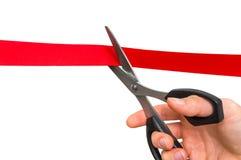Mão com as tesouras que cortam a fita vermelha - cerimônia de inauguração Fotos de Stock