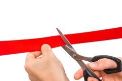 Mão com as tesouras que cortam a fita vermelha - cerimônia de inauguração Fotografia de Stock Royalty Free