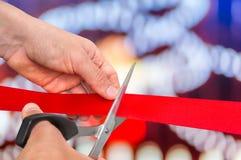 Mão com as tesouras que cortam a fita vermelha - cerimônia de inauguração Imagem de Stock