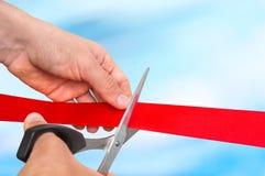 Mão com as tesouras que cortam a fita vermelha - cerimônia de inauguração Imagens de Stock Royalty Free