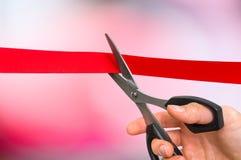 Mão com as tesouras que cortam a fita vermelha - cerimônia de inauguração Imagens de Stock