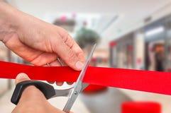 Mão com as tesouras que cortam a fita vermelha - cerimônia de inauguração Foto de Stock Royalty Free