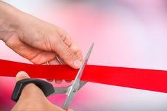 Mão com as tesouras que cortam a fita vermelha - cerimônia de inauguração Fotografia de Stock