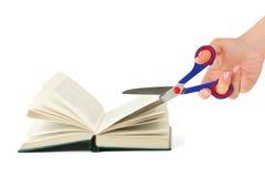 Mão com as tesouras que cortam o livro Foto de Stock