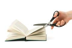 Mão com as tesouras que cortam o livro Fotos de Stock