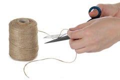 A mão com as tesouras que cortam uma corda Imagens de Stock