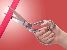 Mão com as tesouras que cortam uma fita vermelha Abertura grande Imagens de Stock Royalty Free