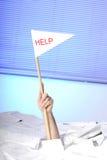 Mão com a bandeira da ajuda que fura fora dos papéis fotos de stock royalty free