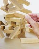 Mão com blocos de apartamentos de queda Fotos de Stock Royalty Free