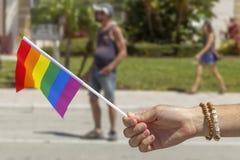 A mão com braceletes guarda uma bandeira do orgulho fotos de stock