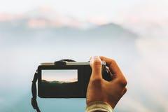Mão com a câmera da foto que toma o tiro das montanhas Foto de Stock Royalty Free