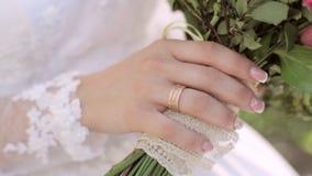 Mão com a casca do casamento da noiva caucasiano que mantém o ramalhete, fim filme