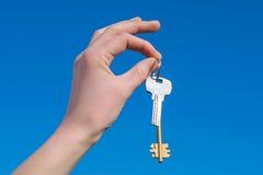 Mão com chave Fotos de Stock Royalty Free