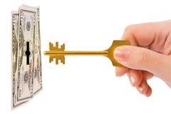 Mão com chave e dinheiro Fotos de Stock