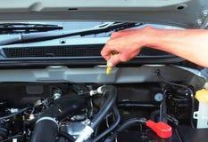 Mão com a chave que verifica o motor de automóveis Fotografia de Stock