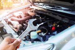 Mão com a chave que verifica o motor de automóveis Foto de Stock