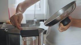 Mão com a colher que agita a sopa de ebulição, close-up vídeos de arquivo