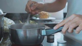 Mão com a colher que agita a sopa de ebulição, close-up filme