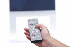 Mão com de controle remoto e aparelho de televisão imagens de stock