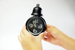 Mão com despertador preto Foto de Stock