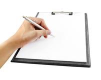 Mão com escrita da pena na prancheta Fotos de Stock