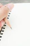 Mão com escrita do lápis algo Fotografia de Stock