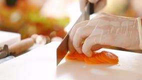 A mão com faca corta a cenoura video estoque