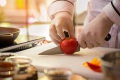 A mão com faca corta o tomate imagens de stock royalty free