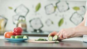 A mão com faca corta vegetais em uma placa de corte de madeira vídeos de arquivo