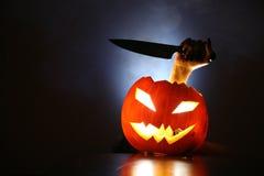 Mão com a faca na Jack-o-lanterna Imagens de Stock