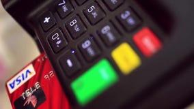 Mão com furto do cartão de crédito através do terminal para filme