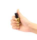 Mão com a garrafa dourada do verniz para as unhas no fundo branco Fotografia de Stock Royalty Free