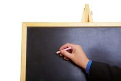 Mão com giz e quadro-negro Imagens de Stock