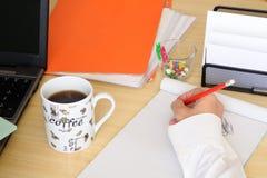 A mão com lápis vermelho toma uma nota no escritório Foto de Stock Royalty Free
