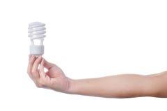 Mão com a lâmpada de poupança de energia no fundo branco Imagens de Stock